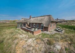 Ferienhaus mit Reetdach und Aussicht auf die Dünen