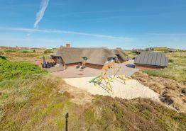 Reetdachhaus mit geschlossener Terrasse und Aktivitätsraum auf einem strandnahen Dünengrundstück